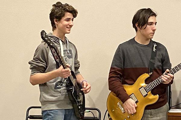 Ragazzi suonano la chitarra all'evewnto School of Rock Verona